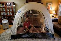 Akash Negi sits in a hypoxic tent, a low-oxygen tent that mimics thin air at high altitude, as he prepares for his Everest expedition