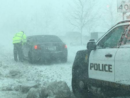 A policeman talks to a driver as snow clogs the roads in Lone Tree Colorado U.S. in this handout