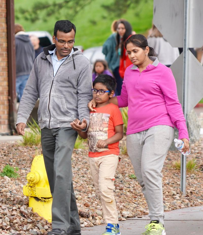 Bharani Rayana, 39, and Madhuri Adari, 32, hold tight to their second-grade son Daksha Rayana 8, following reunification at the Highlands Ranch Recreation Center after a school shooting.