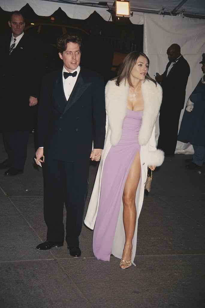 """<p>For her first Met Gala, Elizabeth showed up on the arm of Hugh wearing a pink Versace dress. The theme that year was """"Haute Couture."""" </p>"""