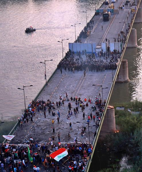 Iraqi Security forces fire tear gas and close the bridge leading to the Green Zone during a demonstration in Baghdad, Iraq, Saturday, Oct. 26, 2019. Iraqi protesters converged on a central square in the capital Baghdad on Saturday as security forces erected blast walls to prevent them from reaching a heavily fortified government area after a day of violence that killed scores. (AP Photo/Hadi Mizban)