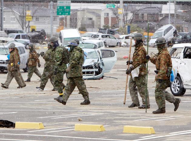 Japan Ground Self Defense Force personnel conduct a search operation following the March 11 earthquake triggered tsunami at the port in Sendai, Japan, Thursday, March 17, 2011. (AP Photo/Mark Baker)