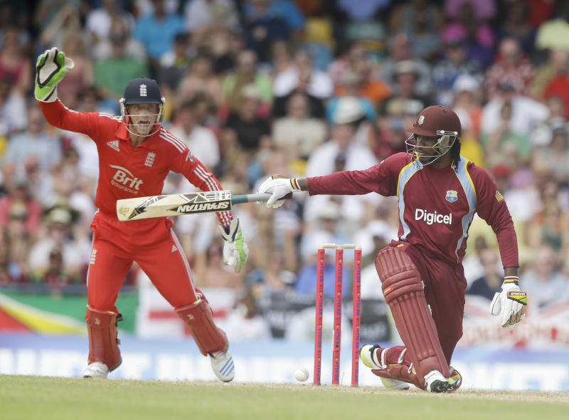 West Indies' Chris Gayle kneels down as he watches his shot as England's wicket keeper Jos Buttler screams during their first T20 International cricket match at the Kensington Oval in Bridgetown, Barbados, Sunday, March 9, 2014. (AP Photo/Ricardo Mazalan)