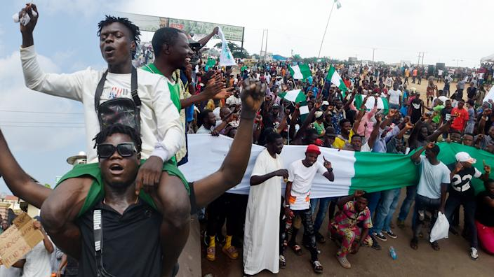 Protesters march at Alausa Secretariat in Ikeja, Lagos State, during a peaceful demonstration against police brutality in Nigeria.  (Photo Illustration: Yahoo News; Photos: Getty Images (2))