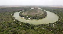 """File - In this July 24, 2014, file photo, a bend in the Rio Grande is viewed from a Texas Department of Public Safety helicopter on patrol over in Mission, Texas. The Biden administration said Friday it will begin work to address risks of flooding and soil erosion from the unfinished wall on the U.S. border with Mexico and provided some answers on how it will use unspent money from shutting down one of President Donald Trump's signature domestic projects. Construction under the Trump administration """"blew large holes"""" into the flood barrier system of low-lying regions in Texas' Rio Grande Valley, the Homeland Security Department said. It said it will """"quickly repair"""" the flood barrier system without extending the wall. Hidalgo County, Texas, officials have expressed alarm about flooding risks during the hurricane season starting in June from breaches in a levee system after Biden halted border wall construction immediately after taking office in January. (AP Photo/Eric Gay, Pool, File)"""