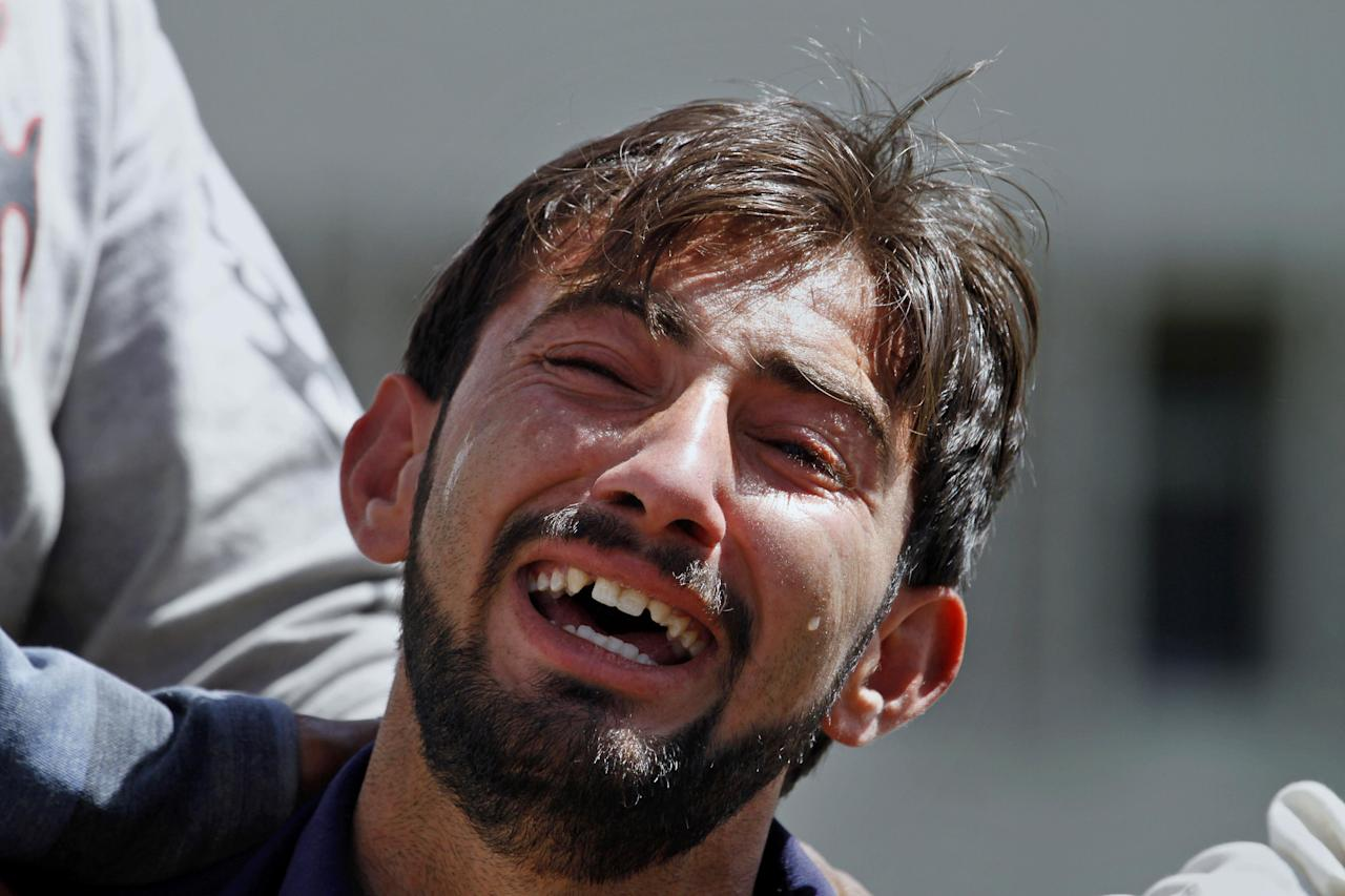 A Pakistani man mourns for a relative killed in a boming, outside a morgue at a local hospital in Islamabad, Pakistan, Wednesday, April 9, 2014. A bomb ripped through a fruit and vegetable market on the outskirts of the Pakistani capital of Islamabad on Wednesday morning, killing and wounding dozens of people, officials said. (AP Photo/Anjum Naveed)