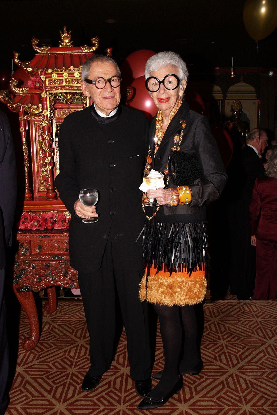 <p>Carl and Iris Apfel attend a birthday party in New York City, with Iris sporting a black fringe skirt with orange fur trim, matching long baubles, and oversized cuffs. <br></p>