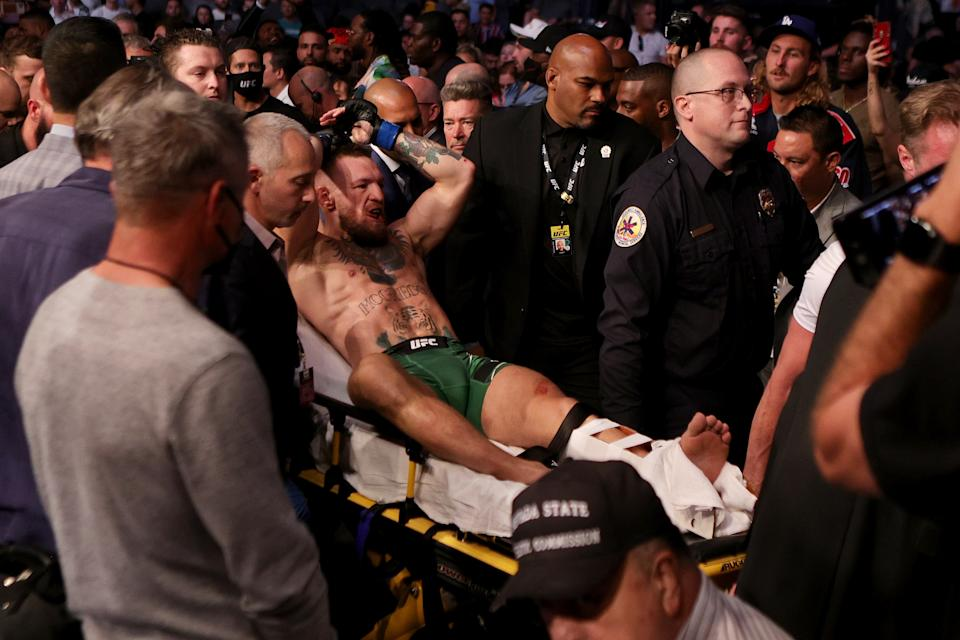 LAS VEGAS, NEVADA - JULY 10: Conor McGregor of Ireland is carried out of the arena on a stretcher after injuring his ankle in the first round of his lightweight bout against Dustin Poirier during UFC 264: Poirier v McGregor 3 at T-Mobile Arena on July 10, 2021 in Las Vegas, Nevada. (Photo by Stacy Revere/Getty Images)