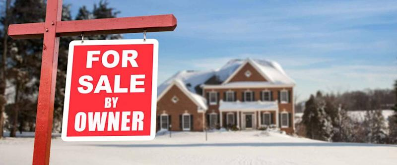 For Sale by owner real estate sign in front of large brick single family house in expansive snow covered yard in mid winter