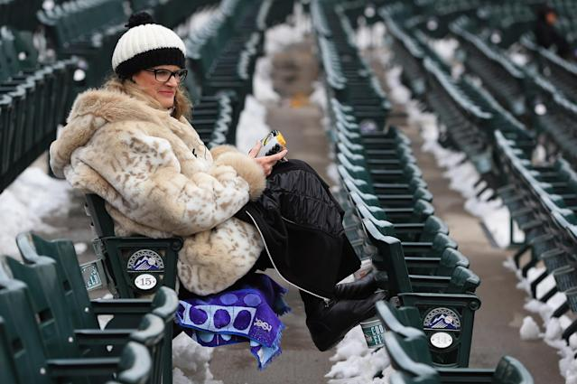 DENVER, CO - APRIL 16: Rockies fan Pegie Frazier of Denver sits in the snow covered seating bowl as snow removal delays the start of the double header between the New York Mets and the Colorado Rockies at Coors Field on April 16, 2013 in Denver, Colorado. All uniformed team members are wearing jersey number 42 in honor of Jackie Robinson Day. (Photo by Doug Pensinger/Getty Images)