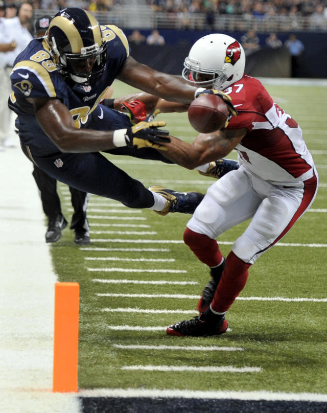 St. Louis Rams tight end Jared Cook, left, dives into the end zone after catching a 16-yard pass for a touchdown as Arizona Cardinals safety Yeremiah Bell defends during the second quarter of an NFL football game on Sunday, Sept. 8, 2013, in St. Louis. (AP Photo/L.G. Patterson)