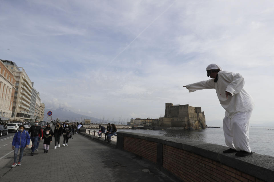 A man wearing the traditional Carnival Neapolitan mask of Pulcinella performs on Via Caracciolo avenue in Naples, Italy, Saturday, Nov. 14, 2020. The regions of Campania and Tuscany were designated red zone on Friday, signaling the dire condition of a hospitals struggling with a surge of new admissions. (AP Photo/Gregorio Borgia)