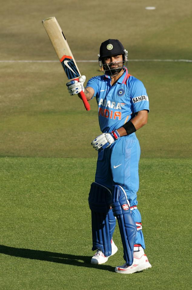 Indian captain Virat Kohli celebrates during the first match of the five match ODI cricket series between India and hosts Zimbabwe at the Harare Sports Club on July 24 2013. AFP PHOTO /Jekesai Njikizana.        (Photo credit should read JEKESAI NJIKIZANA/AFP/Getty Images)