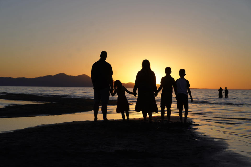 FILE - In this June 13, 2021 file photo, people hold hands as they gather at the receding edge of the Great Salt Lake to watch the sunset near Salt Lake City. The lake has been shrinking for years, and a drought gripping the American West could make this year the worst yet. (AP Photo/Rick Bowmer)
