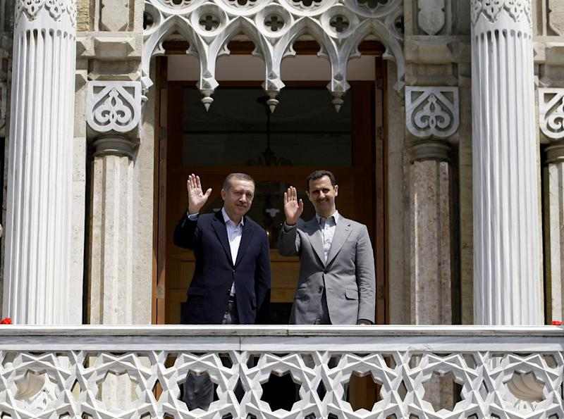 FILE - In this May 9, 2010 file photo, Syrian President Bashar Assad, right, and Turkish Prime Minister Recep Tayyip Erdogan wave to the media before a meeting at the Ottoman-era Ciragan Palace in Istanbul, Turkey. Mustafa Kemal Ataturk, Turkey's independence war hero, national founder in a time of crisis, imposer of secular ideas on a mostly Muslim population and a hallowed presence long after his death. The cult of Ataturk, once a staple of Turkish state ideology, is slowly, sometimes imperceptibly, being diluted, replaced in part by the Ottoman imperial era as inspiration for a government with its own set of ideas about modernity, morality and regional stature.(AP Photo/Ibrahim Usta, File)