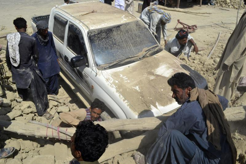 Survivors remove the rubble of a mud house from a vehicle after it collapsed following an earthquake in the town of Awaran