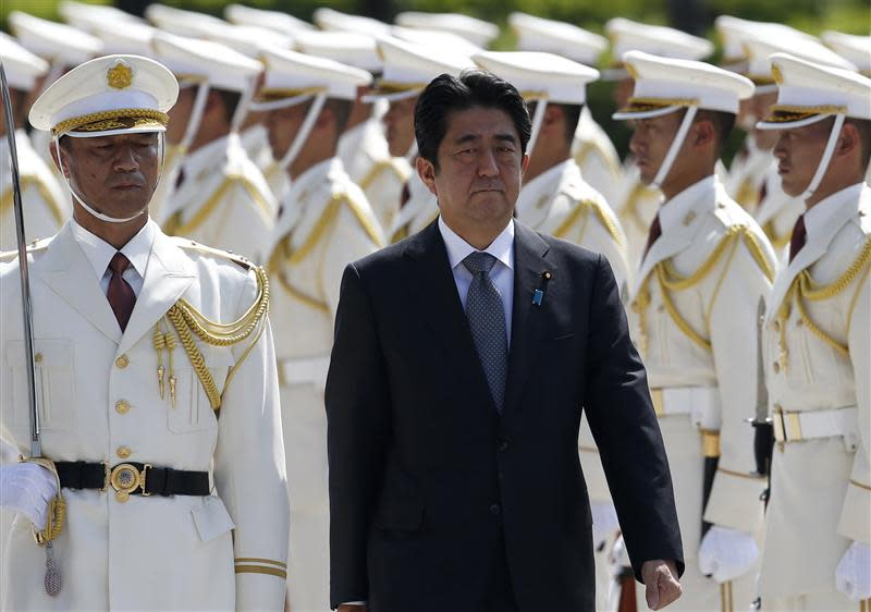 Japan's Prime Minister Shinzo Abe reviews the honour guard before a meeting with Japan Self-Defense Force's senior members at the Defense Ministry in Tokyo