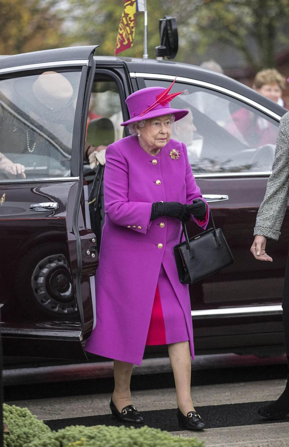 <p>The Queen arrived at an army barracks in a bright mix of purple and pink.<br><i>[Photo: PA]</i> </p>