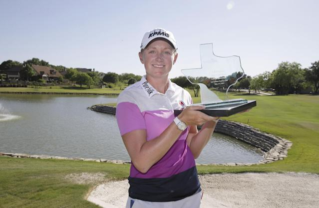 Stacy Lewis posses for photos with the trophy after winning the North Texas LPGA Shootout golf tournament at the Las Colinas Country Club in Irving, Texas, Sunday, May 4, 2014. (AP Photo/LM Otero)