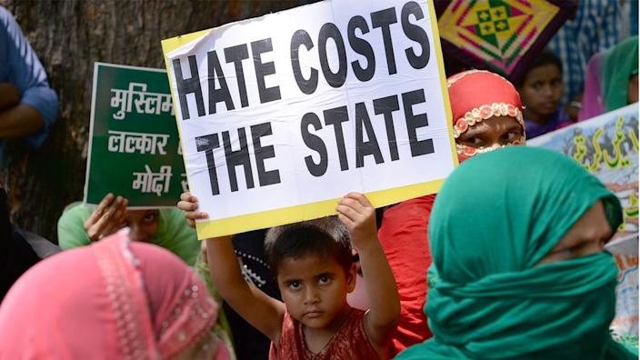 A young Indian demonstrator holds a placard at a rally in Delhi in 2017 in protest over a spate of assaults against Muslims and low-caste Dalits by Hindu vigilantes
