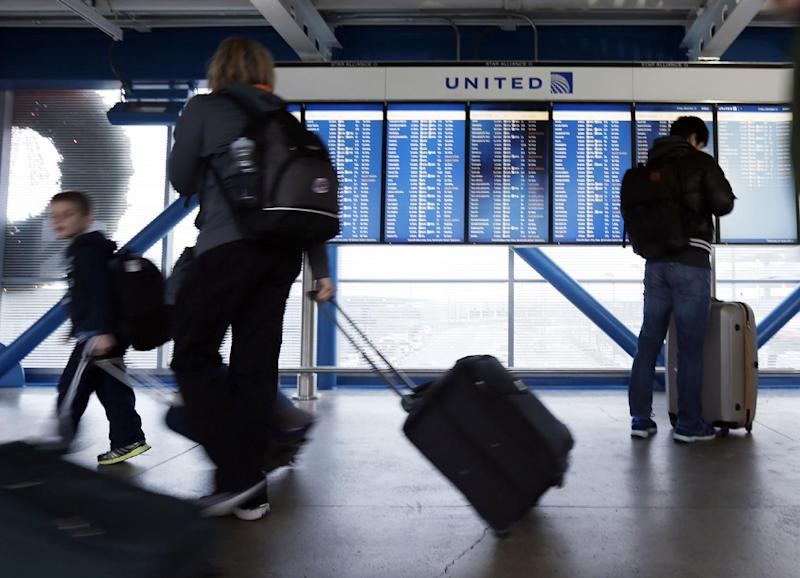 FILE - In this Friday, Dec. 21, 2012, file photo, travelers walk in front of an United Airline flight information screen at O'Hare airport in Chicago. A massive winter storm is disrupting travel plans for tens of thousands of fliers trying to get home after Christmas on Wednesday, Dec. 26, 2012. Snow, thunderstorms, sleet, tornados and high winds have grounded planes in the nation's midsection and are expected to slow operations on the East Coast.(AP Photo/Nam Y. Huh)