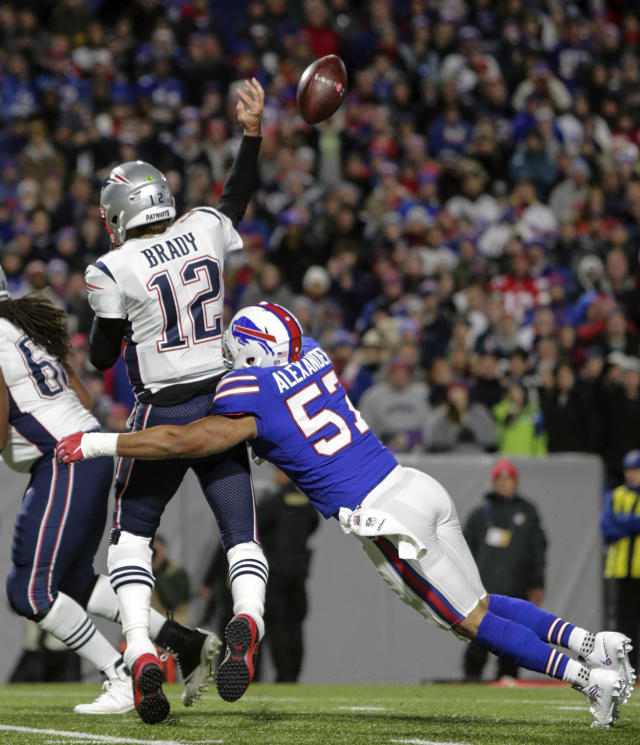 FILE - In this Oct. 29, 2018, file photo, New England Patriots quarterback Tom Brady (12) is hit from behind by Buffalo Bills linebacker Lorenzo Alexander (57) during an NFL football game in Orchard Park, N.Y. The Bills play at the patriots on Sunday. The Patriots can lock up a 10th consecutive division title this week with a win or tie against Buffalo. (AP Photo/Chris Cecere, File)