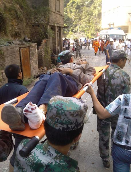 In this photo provided by Xinhua News Agency, an injured villager is carried on a stretcher by rescuers following an earthquake in Luozehe Town, Yiliang County, southwest China's Yunnan Province, Friday, Sept. 7, 2012. A series of earthquakes collapsed houses and triggered landslides in a remote mountainous part of southwestern China on Friday, killing dozens of people with the toll expected to rise. Damage was preventing rescuers from reaching some outlying areas, and communications were disrupted. (AP Photo/Xinhua, Zhou Hongpeng) NO SALES