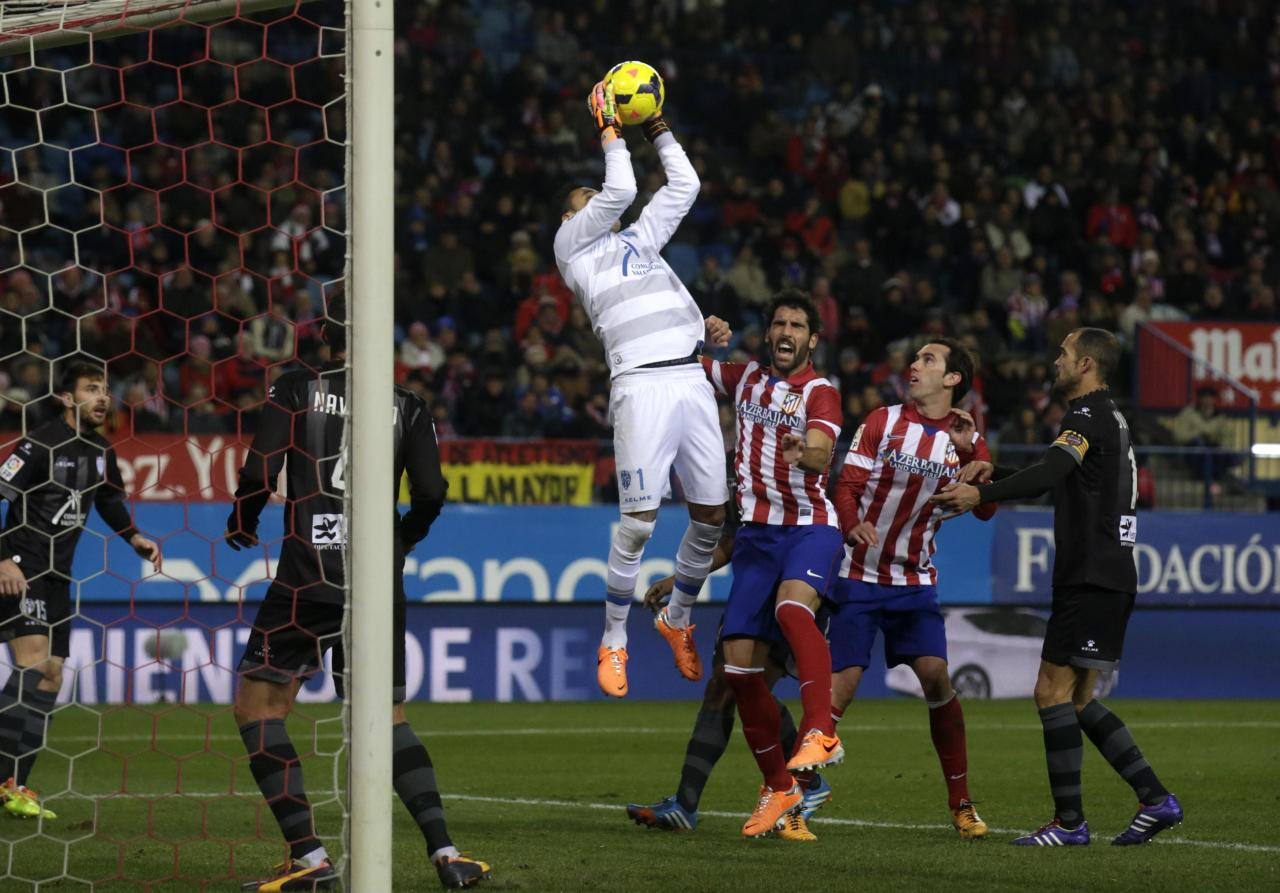 Levante's goalkeeper Keylor Navas (C) catches a ball in front of Atletico Madrid players during their Spanish first division soccer match at Vicente Calderon stadium in Madrid December 21, 2013. REUTERS/Andrea Comas (SPAIN - Tags: SPORT SOCCER)