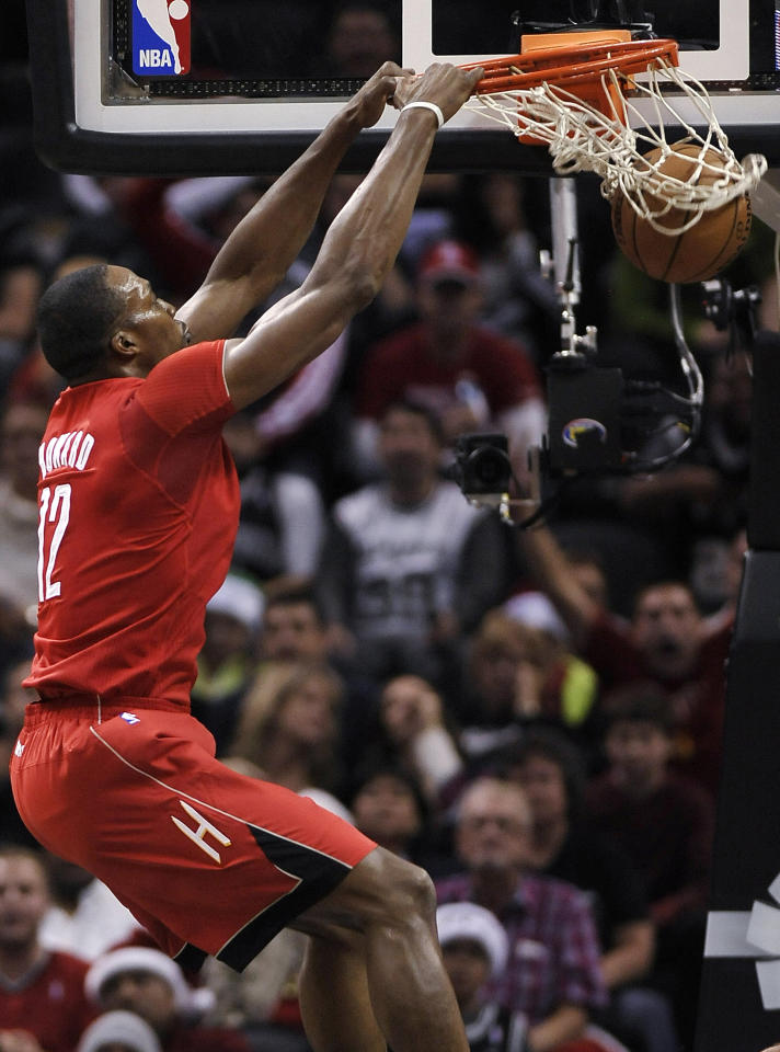 Houston Rockets forward Dwight Howard dunks during the first half of an NBA basketball game against the San Antonio Spurs on Wednesday, Dec. 25, 2013, in San Antonio. (AP Photo/Darren Abate)