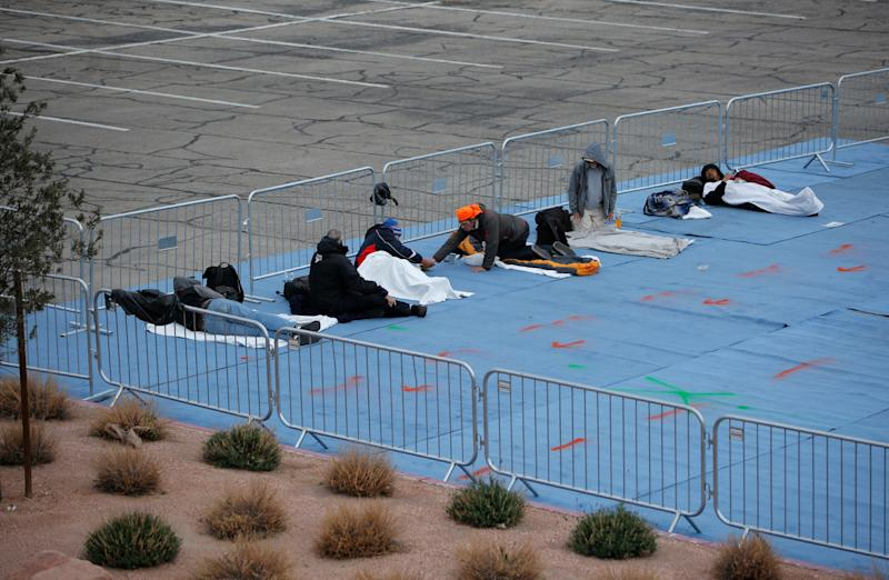 People rest at a makeshift camp for the homeless Saturday, March 28, 2020, in Las Vegas. Officials opened part of a city parking lot as a makeshift homeless shelter after a local shelter closed when a man staying there tested positive for the coronavirus. (AP Photo/John Locher)