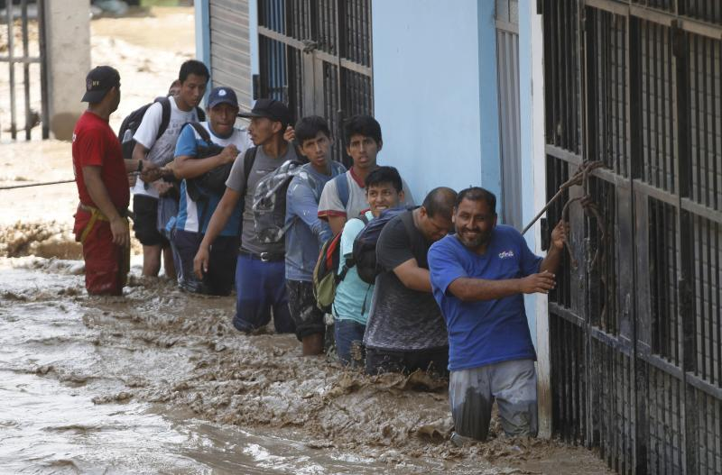 A group of people, stranded in flood waters, hold onto a rope as they walk to safety in Lima, Peru, Friday, March 17, 2017. Intense rains and mudslides over the past three days have wrought havoc around the Andean nation and caught residents in Lima, a desert city of 10 million where it almost never rains, by surprise. (AP Photo/Martin Mejia)