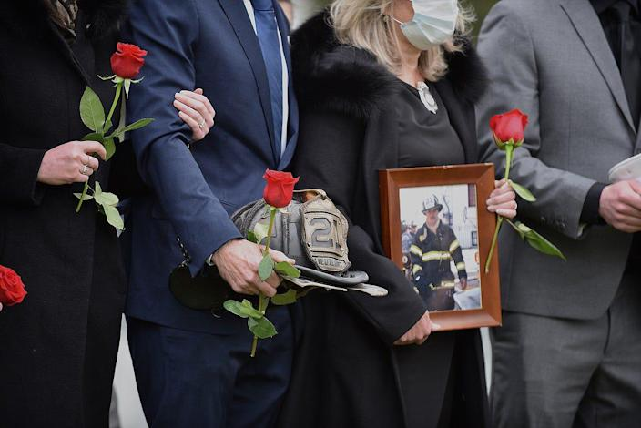 New Rochelle, New York, firefighters line up at the cemetery following the funeral of Captain Andy DiMaggio May 7, 2020. DiMaggio died of complications from the coronavirus.