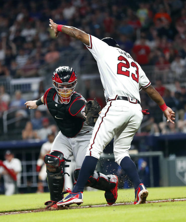 Atlanta Braves' Danny Santana (23) is tagged out by Cincinnati Reds catcher Tucker Barnhart (16) after being caught in a rundown between third base and home on an Ender Inciarte ground ball in the sixth inning of a baseball game Monday, June 25, 2018, in Atlanta. (AP photo/John Bazemore)