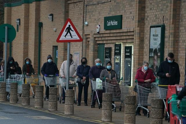 Customers queuing outside a Morrisons supermarket