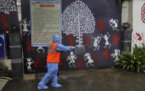 A civic worker sanitizes the gate of Bollywood superstar Amitabh Bachchan's residence after Bachchan and his son tested positive for the coronavirus and were hospitalized in Mumbai, India, Sunday, July 12, 2020. (AP Photo/Rafiq Maqbool)