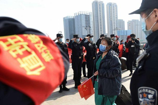 PHOTO: Police officers salute as a medical worker from outside Wuhan arrives at the Wuhan Railway Station before leaving the epicenter of the novel coronavirus disease outbreak, in Hubei province, China, March 17, 2020. (Reuters)