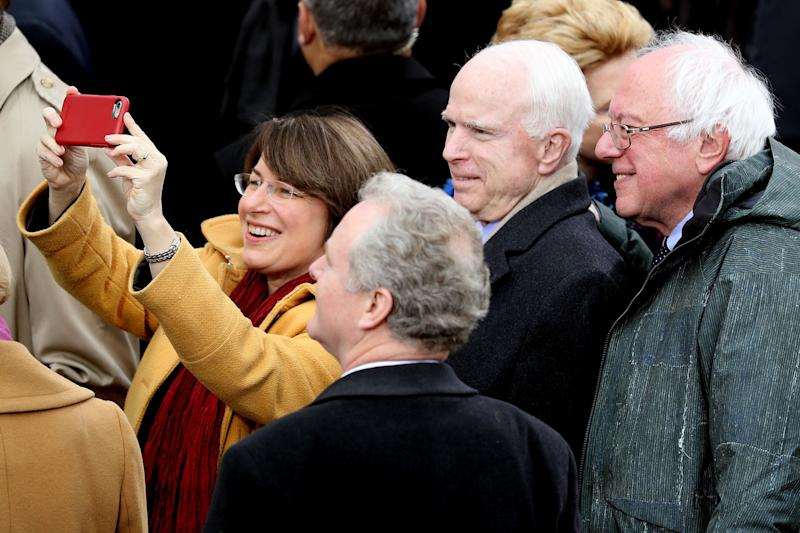 Sen. Amy Klobuchar (D-Minn.) takes a selfie with (from right) Sens. Bernie Sanders (I-Vt.), the late John McCain (R-Ariz.) and Chris Van Hollen (D-Md.) during President Donald Trump's inauguration in 2017. (Photo: Joe Raedle via Getty Images)