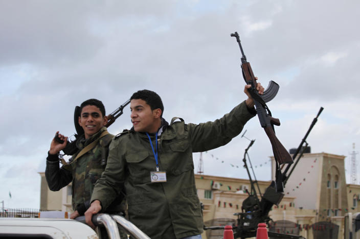 Libyan gunmen celebrate on the early morning of the second anniversary of the revolution that ousted Moammar Gadhafi, in Benghazi, Libya, Sunday, Feb, 17, 2013. (AP Photo/Mohammad Hannon)