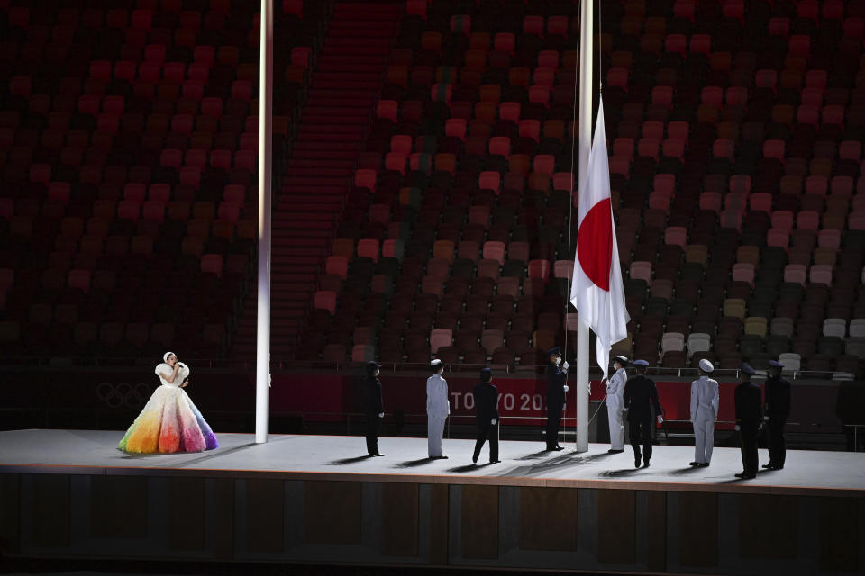 The Japanese flag is hoisted as Misia sings the national anthem during the opening ceremony in the Olympic Stadium at the 2020 Summer Olympics, Friday, July 23, 2021, in Tokyo, Japan. (Dylan Martinez/Pool Photo via AP)