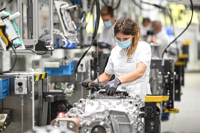 12 May 2020, Baden-Wuerttemberg, Friedrichshafen: At plant two of the automotive supplier ZF Friedrichshafen, mechanic Vanessa is working on a transmission for trucks called ZF Traxon. ZF Friedrichshafen slowly restarts operations with protective and hygienic measures. Every worker wears a mouth and nose guard, minimum distances are marked on the floor and some workplaces are separated by plexiglass panels. Photo: Felix Kästle/dpa (Photo by Felix Kästle/picture alliance via Getty Images)