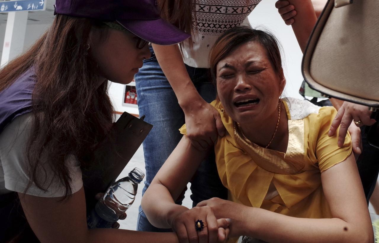 Volunteers comfort a crying woman at a caring centre for relatives of victims of a factory explosion, in Kunshan, Jiangsu province August 3, 2014. China suffered its worst industrial accident in a year on Saturday when an explosion killed at least 69 people and injured more than 120 at a factory that makes wheels for U.S. carmakers, including General Motors. REUTERS/Mo Yat (CHINA - Tags: DISASTER BUSINESS TRANSPORT) CHINA OUT. NO COMMERCIAL OR EDITORIAL SALES IN CHINA