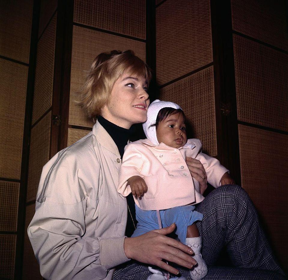 <p>May cradles her four-month-old daughter, Tracey Davis, while arriving in Stockholm, Sweden, for a visit with her parents in 1961. It was the first time the actress's parents met her child with singer Sammy Davis, Jr.</p>