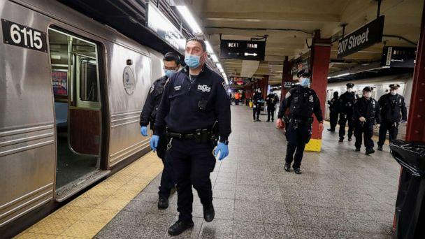 PHOTO: NYPD and MTA officers search cars for sleeping passengers and direct them to the exits at the 207th Street A-train station, April 30, 2020, in the Manhattan borough of New York. (John Minchillo/AP)