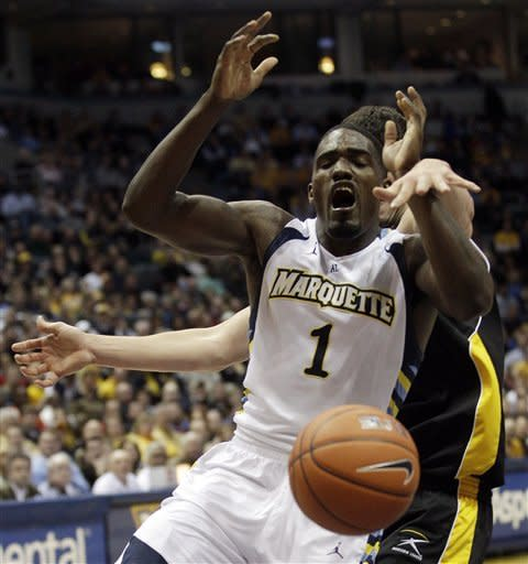 Marquette's Darius Johnson-Odom (1) has the ball stripped away by Wisconsin Milwaukee's Tony Meier during the first half of an NCAA college basketball game on Thursday, Dec. 22, 2011, in Milwaukee. (AP Photo/Morry Gash)