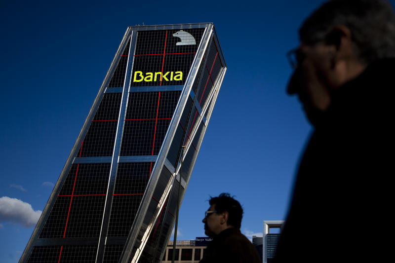FILE - In this Nov. 28, 2012 file photo, people walk near the Bankia bank headquarters in Madrid. Spain's economy ministry says euro 39.5 billion ($51.3 billion) in bailout aid approved by European authorities for troubled Spanish banks has arrived. A ministry spokeswoman said Wednesday Dec. 12, 2012, the money is now in the hands of a state-run fund set up to help those entities worst hit by the property market collapse in 2008. The funds are part of a euro 100 billion rescue package earmarked for Spain by the other 16 European Union countries that use the euro. The package is designed to ease the pressure on the government so it can concentrate on managing national finances and avoid a full-blown sovereign bailout.(AP Photo/Daniel Ochoa de Olza, File)