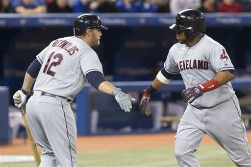 Cleveland Indians' Carlos Santana, right, is congratulated by Mark Reynolds after hitting a home run off Toronto Blue Jays' Mark Buehrle during the fourth inning of a baseball game in Toronto on Thursday, April 4, 2013. (AP Photo/The Canadian Press, Chris Young)