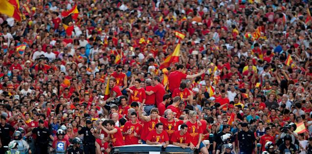 MADRID, SPAIN - JULY 02: Spain players celebrate with their fans and the UEFA EURO 2012 trophy on a double-decker bus during the Spanish team's victory parade on July 2, 2012 in Madrid, Spain. Spain beat Italy 4-0 in the UEFA EURO 2012 final match in Kiev, Ukraine, on July 1, 2012. (Photo by Pablo Blazquez Dominguez/Getty Images)
