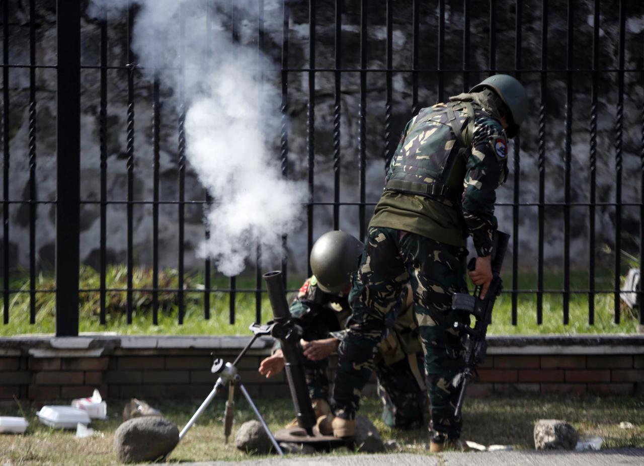 Government soldiers of Task Force Zamboanga (TFZ) fire a 60mm mortar round towards the Muslim rebels of Moro National Liberation Front (MNLF) positions in Zamboanga city in southern Philippines September 16, 2013.REUTERS/Erik De Castro (PHILIPPINES - Tags: CIVIL UNREST CONFLICT POLITICS MILITARY)
