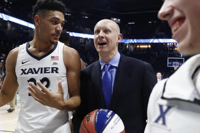 Xavier head coach Chris Mack, center, smiles alongside Kaiser Gates (22) after becomes the winningest coach in Xavier history Wednesday, Jan. 17, 2018, in Cincinnati. Xavier won 88-82. (AP)