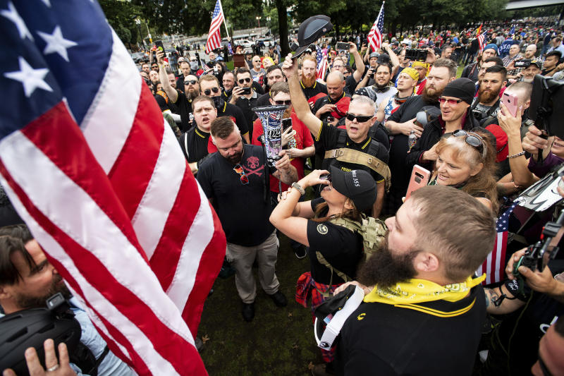 """Members of the Proud Boys and other right-wing demonstrators plant a flag in Tom McCall Waterfront Park during an """"End Domestic Terrorism"""" rally in Portland, Ore., on Saturday, Aug. 17, 2019. Portland Mayor Ted Wheeler said the situation was """"potentially dangerous and volatile"""" but as of early afternoon most of the right-wing groups had left the area via a downtown bridge and police used officers on bikes and in riot gear to keep black clad, helmet and mask-wearing anti-fascist protesters — known as antifa — from following them. (AP Photo/Noah Berger)"""